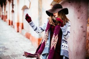 Ragazza che indossa un cardigan sui toni dell'azzurro con motivi invernali abbinato ad una maxi sciarpa e cappello a tesa larga nelle fantasie del vinaccia e marrone