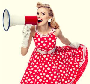 Ragazza con abito a campana rosso a pois bianchi anni 50 in abbinamento a cintura e guanti bianchi