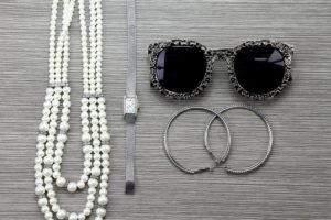 Accessori vari donna sui toni del grigio argento. Collana di perle, orologio, orecchini ad anello e occhiali da sole
