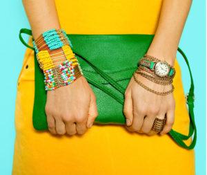 Particolare di polsi e mani di una ragazza bigiotteria etnica molto vistosa e mini bag verde smeraldo su abito giallo vivo
