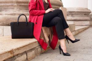 Particolare di gambe di una ragazza con pantaloni neri, canotta bordeaux. Accessori: décolleté nere a tacco alto e e shopper in pelle nera