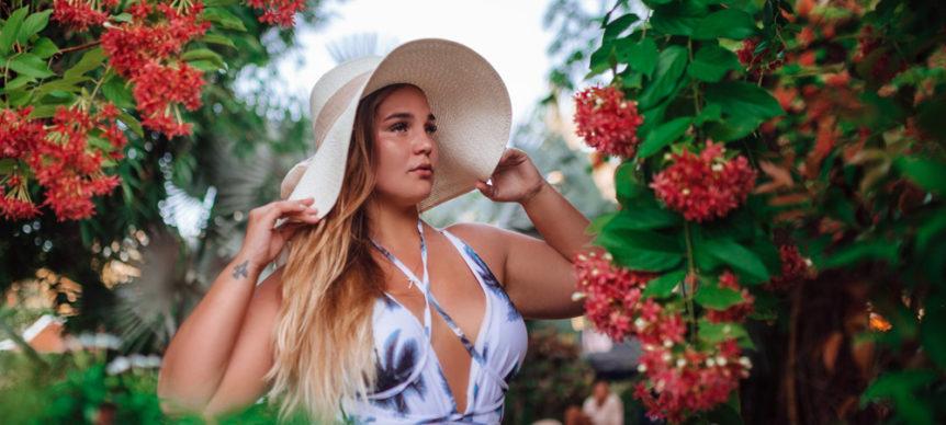 Modella curvy con cappello a tesa larga e abito bianco a fantasia scollato