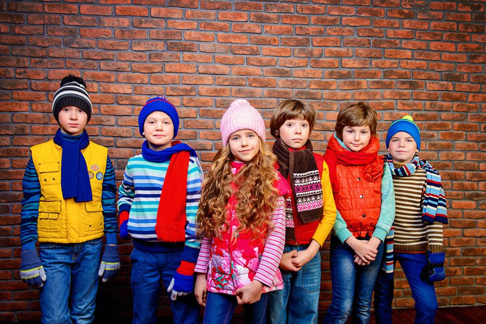 Foto di gruppo di bimbi in abbigliamento invernale. Jeans, maglioni e cappelli in lana colorati