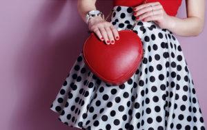 Primo piano di gonna bianca a pois neri abbinata ad un t shirt rossa e mini bag in tinta a forma di cuore con tracolla a catenella