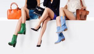 Gambe di 3 ragazze sedute con borse e scarpe di vari modelli e colori