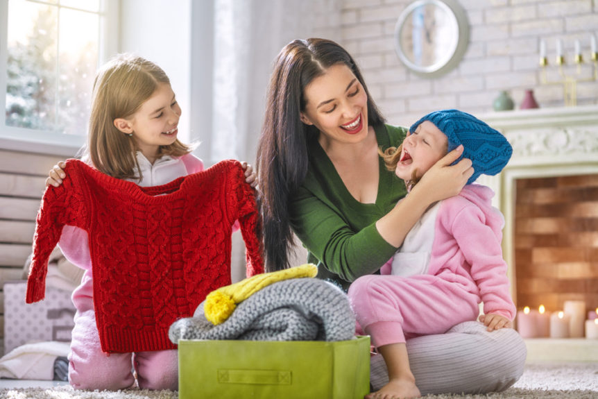 Moda bimbi inverno. Mamma con due bimbi che scelgono nuovi vestiti