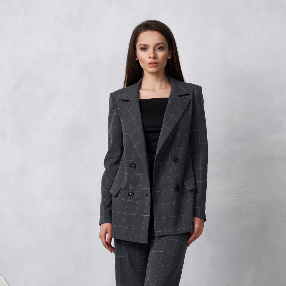 Ragazza che indossa un completo pantaloni con blazer a scacchi sui toni del grigio fumo abbinato a sottogiacca nero con scollo a barca