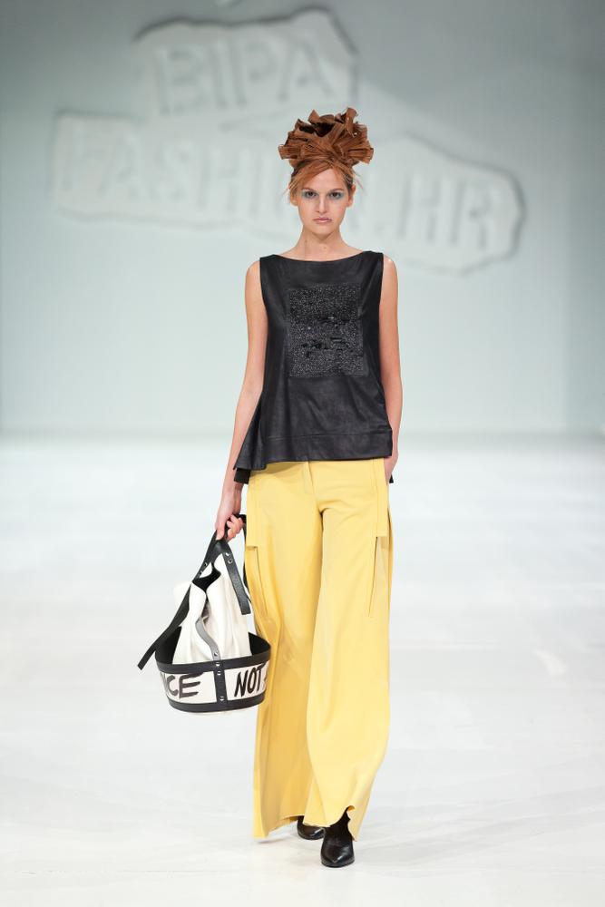 Ragazza che indossa ampi pantaloni a palazzo di colore giallo in abbinamento ad un top lungo asimmetrico di colore nero. Completano l'outfit scarpe nere a tacco alto e borsa secchiello nei colori del bianco e nero
