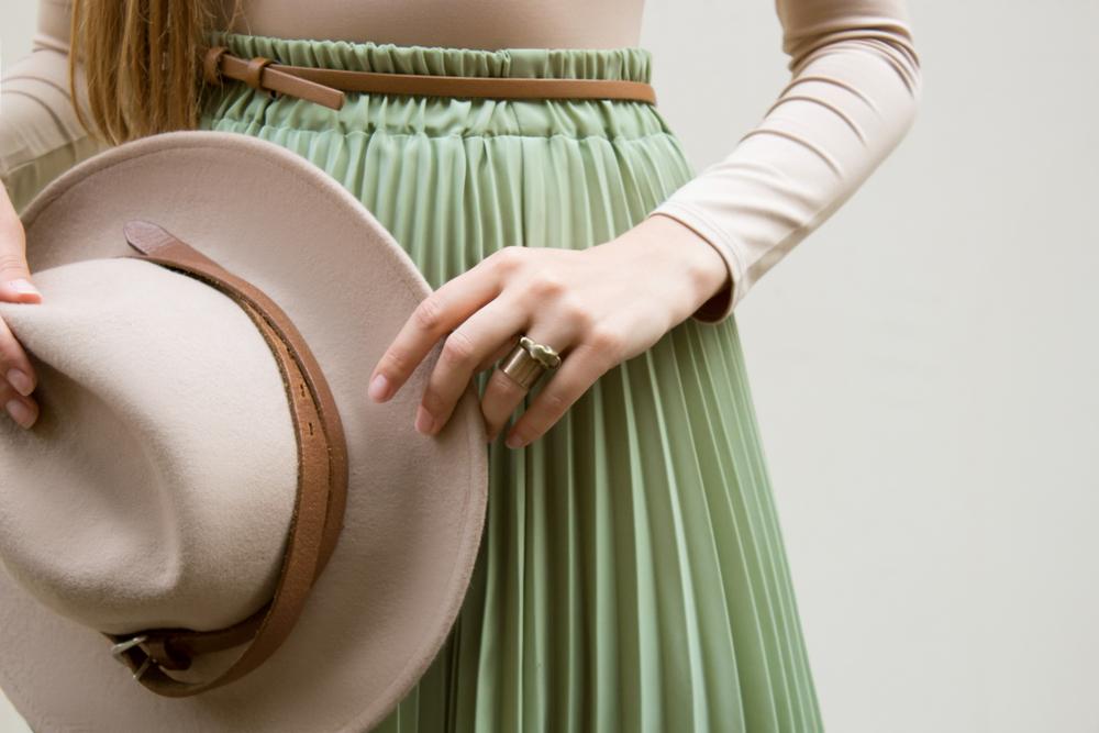 Particolare di gonna plissettata verde menta pastello con maglia e cappello a tesa larga beige