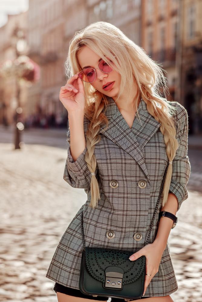 Immagine a mezzo busto di una ragazza bionda che indossa un blazer fantasia a scacchi sui toni del marrone abbinata ad una mini bag nera