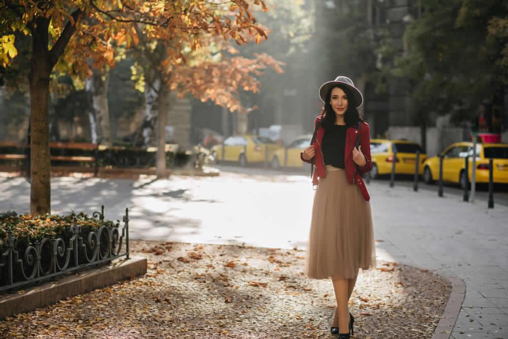 Ragazza in un parco in autunno. Indossa una gonna in tulle sotto il ginocchio abbinata ad un sottogiacca nero e giacca rosso ciliegia. Completano l'outfit cappello modello borsalino azzurro polvere e décolleté nere.