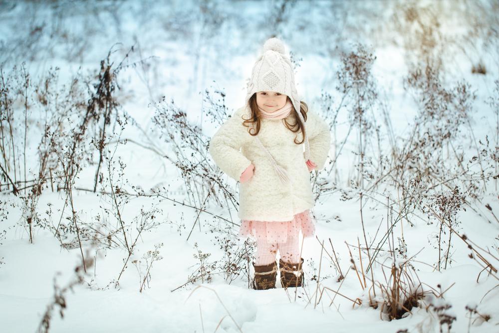 Bimba nella neve con piumino e cappello bianco e vestitino rosa con volant