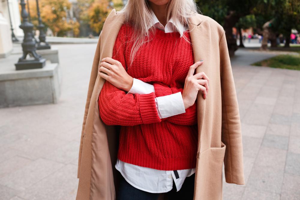 Ragazza che indossa una camicia bianca abbinata ad un maglione rosso e cappotto beige