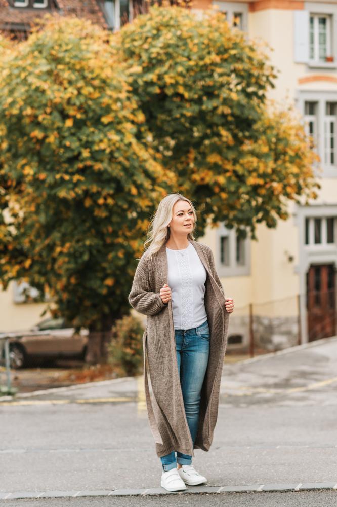 Ragazza a figura intera con sfondo di villa e albero autunnale. Indossa un cardigan lungo color cammello abbinato a jeans blu a sigaretta e t shirt bianca