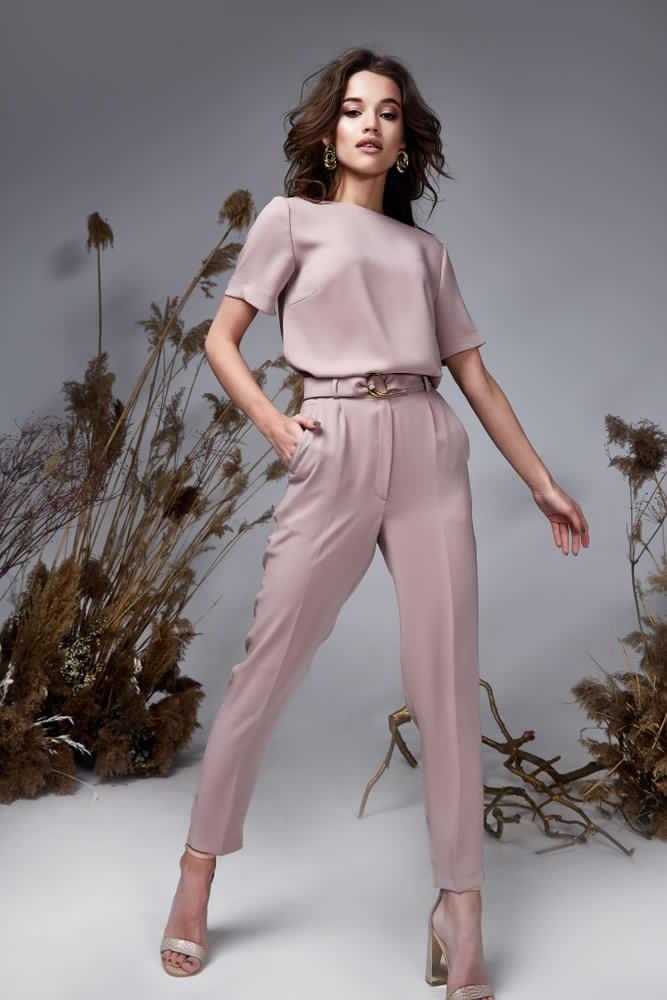 Ragazza che indossa pantaloni rosa cipria con pinces abbinati a cintura in tessuto tono su tono e camicetta in seta dello stesso colore a manica corta. Completano l'outfit sandali a tacco alto tono su tono