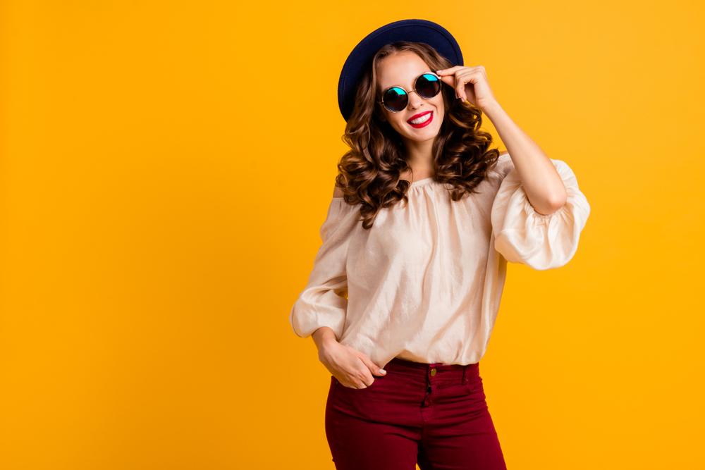 Immagine a mezzo busto di ragazza che indossa una camicetta in seta color champagne con maniche a sbuffo e pantaloni rosso bordeaux