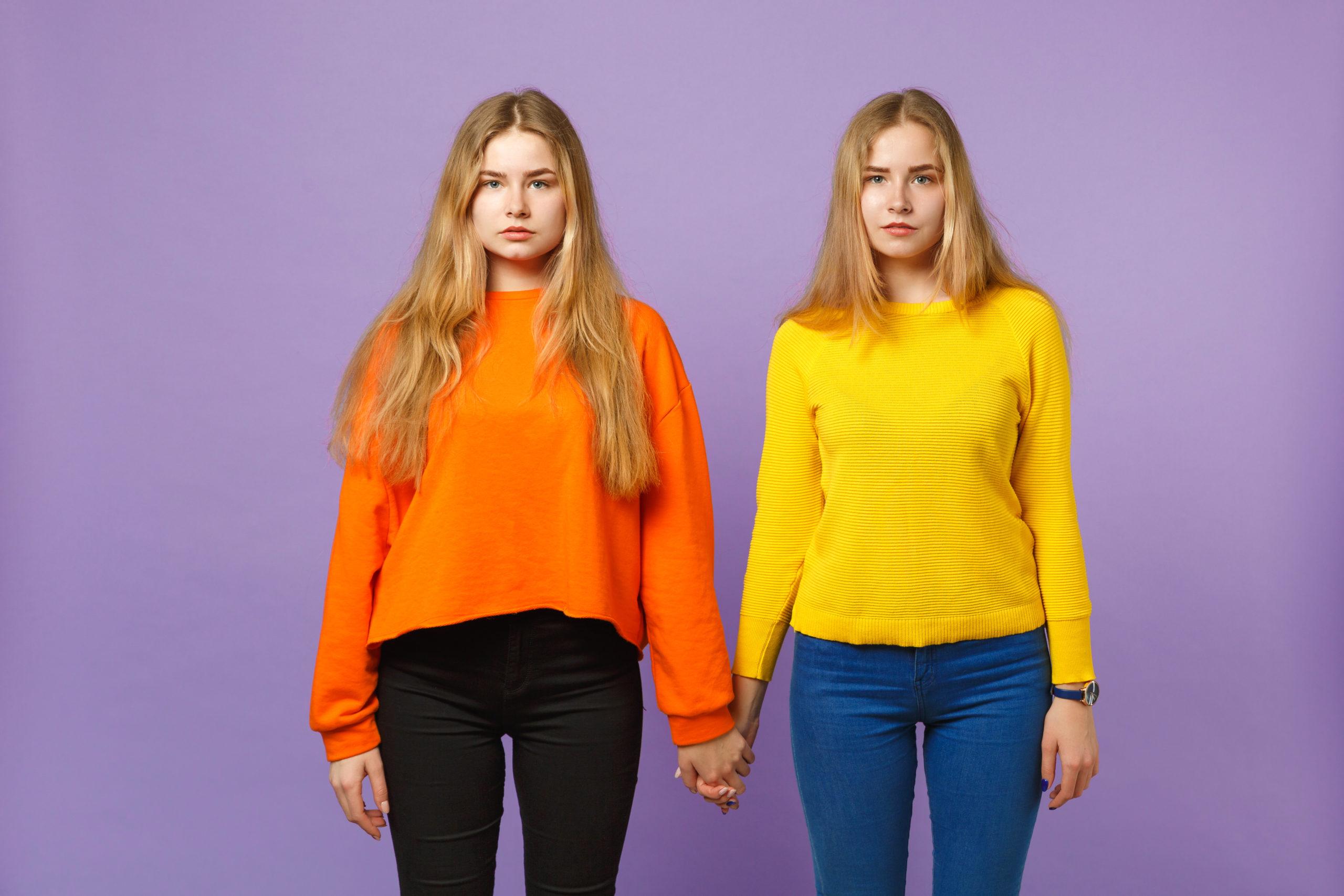 Coppia di ragazze che indossano accostamenti di due colori. Pantaloni neri e maglioncino arancio e pantaloni jeans blu e maglioncino giallo