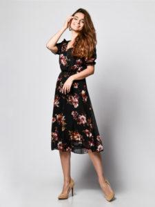Ragazza con un vestito a fiori a maniche corte. Indossa décolleté a tacco alto di colore beige