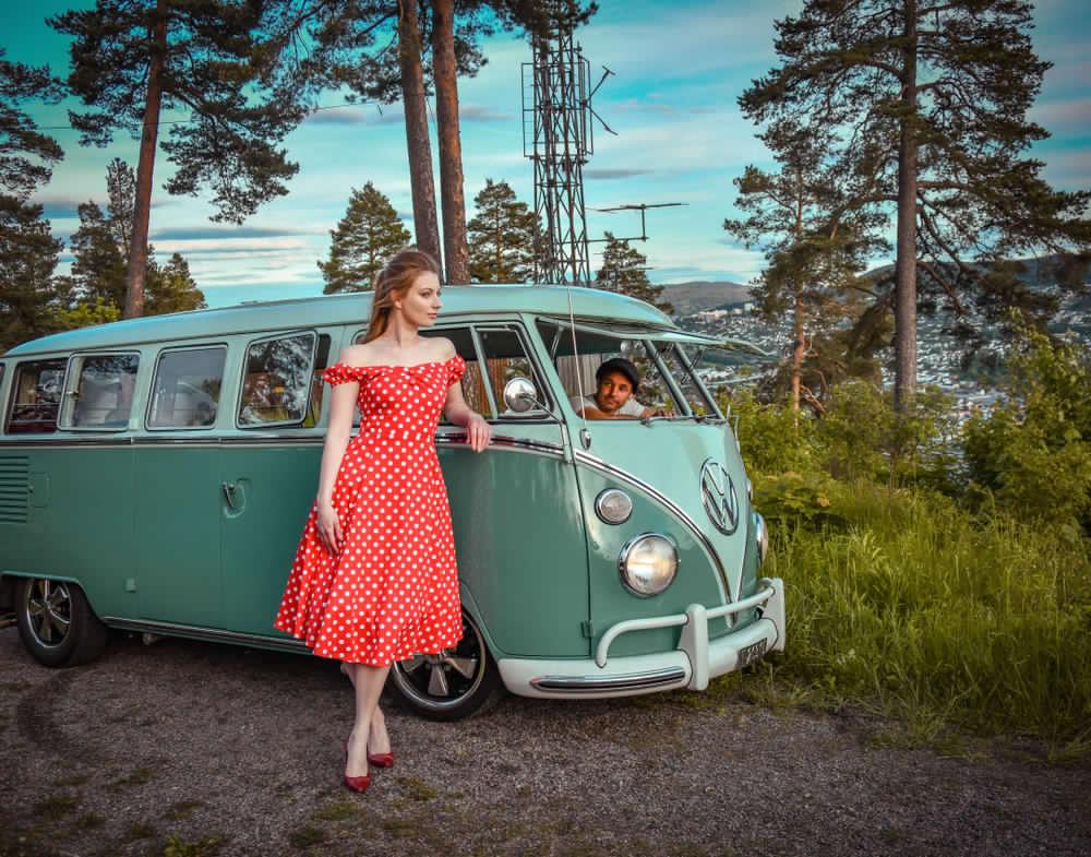 Immagine di una ragazza appoggiata ad un vecchio furgone Wolkwagen anni 50 color verde salvia. La ragazza indossa un abito rosso a pois bianchi senza spalline modello a campana anni 50, in abbinamento a décolleté a tacco alto di colore rosso