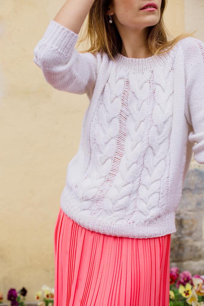 Ragazza che indossa un maxi pull in lana bianca a trecce abbinato ad una gonna plissettata rosa shocking