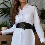 Ragazza che indossa una camicia bianca lunga con grande cintura in pelle