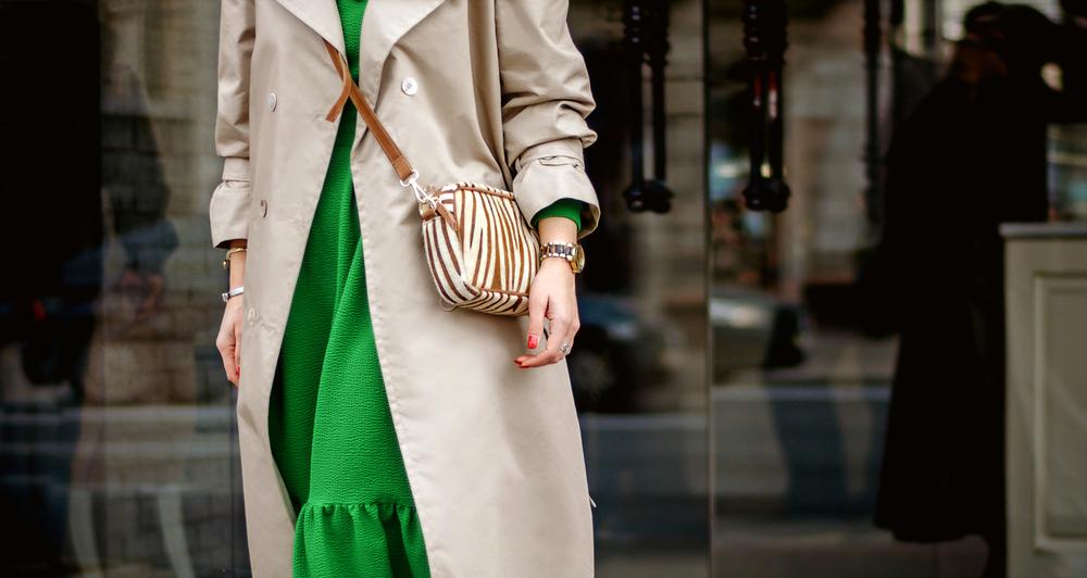 Particolare di abito verde abbinato a trench crema e mini bag crema e marrone