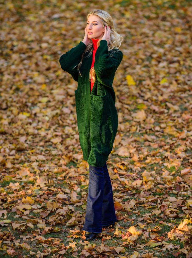Ragazza a figura intera in un prato autunnale che indossa un cardigan verde lungo, maglione rosso vivo e jeans blu a zampa di elefante