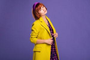 Cappotto giallo sole con abito a fantasia sui toni del nero, rosa e rosso