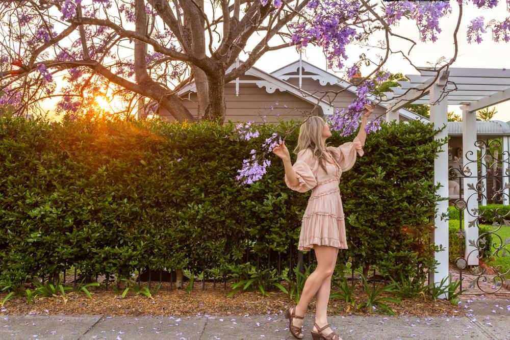 Ragazza dietro una siepe che indossa un abito corto con maniche a sbuffo color rosa cipria e ruches sulla gonna. Completano l'outfit sandali a tacco basso in cuoio color cognac