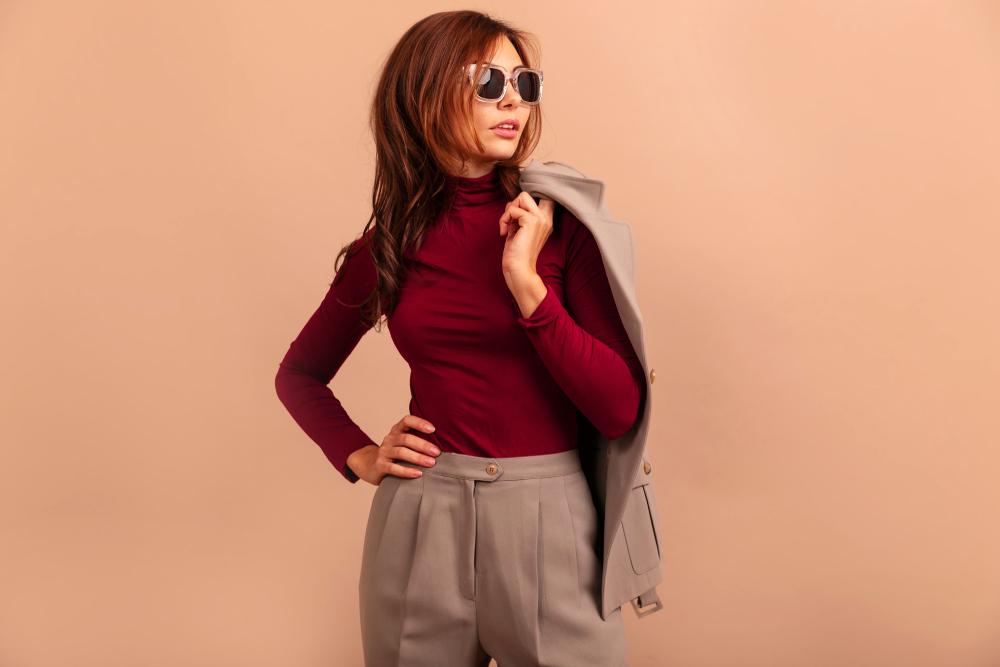 Ragazza che indossa pantaloni e giacca beige abbinati ad un maglione rosso a collo alto