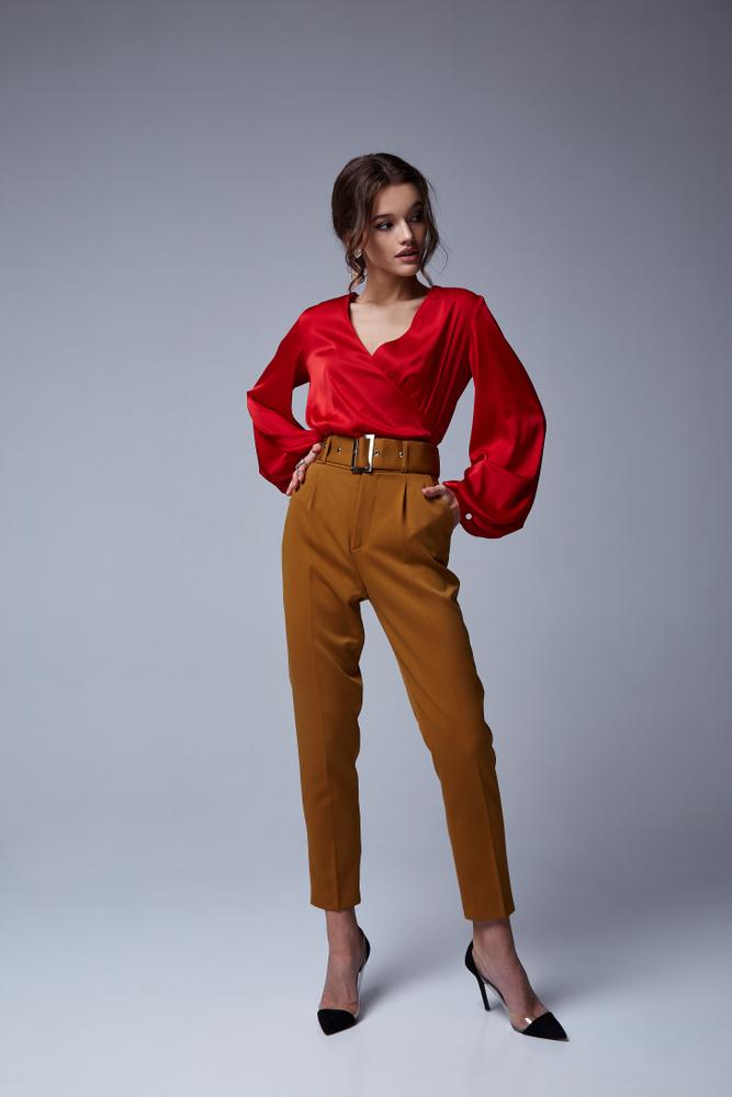 Immagine di ragazza a figura intera che indossa pantaloni color cognac con cintura alta e camicetta in raso rossa con maniche a sbuffo e scollo a V. Scarpe décolleté nere con tacco alto e fascia oro.