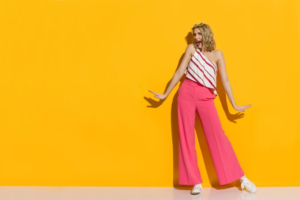Ragazza che indossa pantaloni a palazzo colore rosa e top monospalla con volant e fantasia a righe oblique. In abbinamento sneakers bianche con lacci a fiocco.