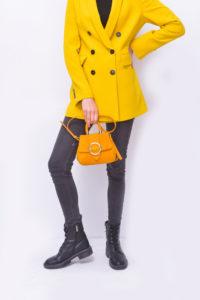 Ragazza che indossa jeans neri aderenti e giacca con collo sciallato giallo sole. In abbinamento mini bag ocra e anfibi neri