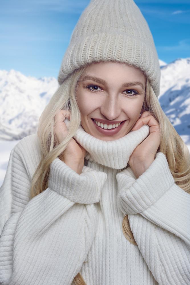 Primo piano di ragazza che indossa un ampio maglione invernale bianco con collo alto e cappello in lana coordinato.
