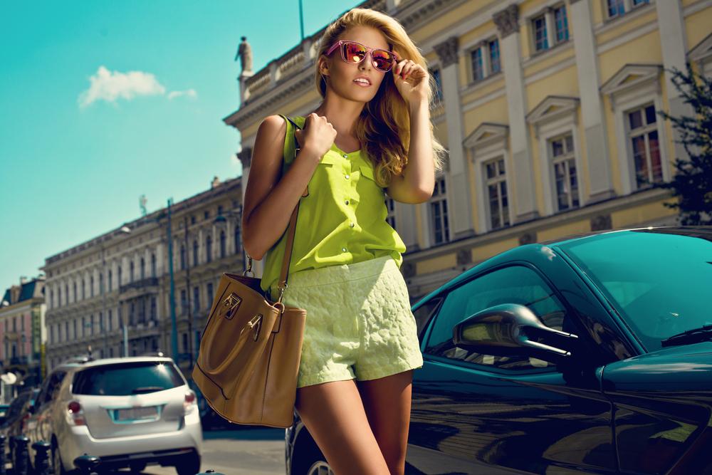 Ragazza in una via cittadina che indossa shorts giallo limone abbinati ad una camicetta tono su tono con volant sul davanti. Completa l'outfit una ampia borsa color cognac