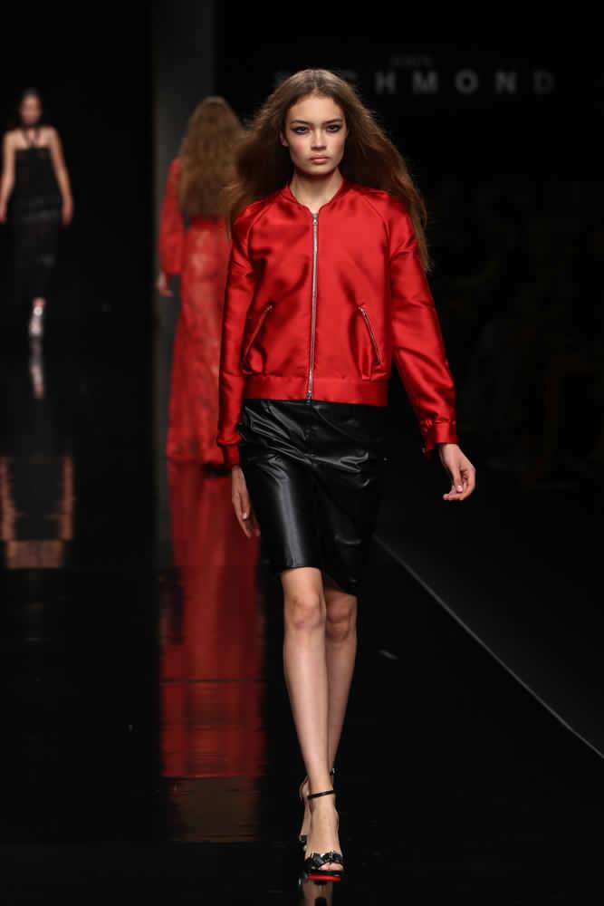 Immagine tratta da una sfilata di moda. La ragazza indossa una gonna a tubino midi di colore nero in tessuto lucido abbinata ad un bomber rosso ciliegia con cerniera sempre lucido. Le scarpe sono sandali a tacco alto neri con inserti rossi.