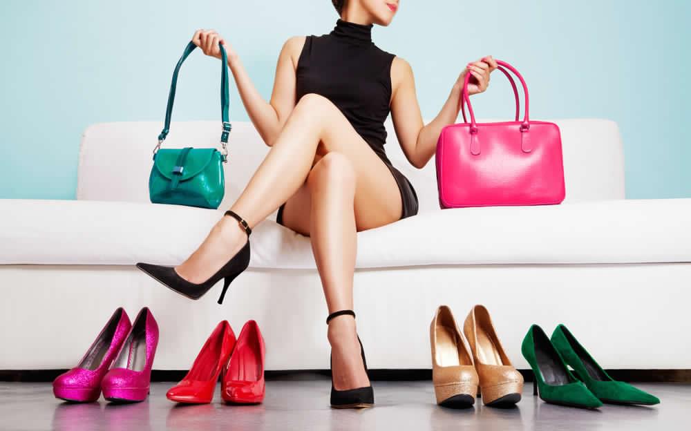 Ragazza seduta su un divano bianco che tiene nelle mani due borse di colore rosa acceso e verde. Ai suoi piedi 4 paia di scarpe donna a tacco alto di vari colori (fucsia, rosso, nude con zeppa e verde smeraldo)