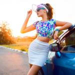 Ragazza al tramonto appoggiata ad un auto che indossa mini gonna bianca e top corto multicolor
