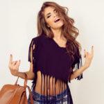 Immagine a mezzo busto di ragazza che indossa un top corto nero con frange abbianto a jeans blu e borsa bauletto color cognac