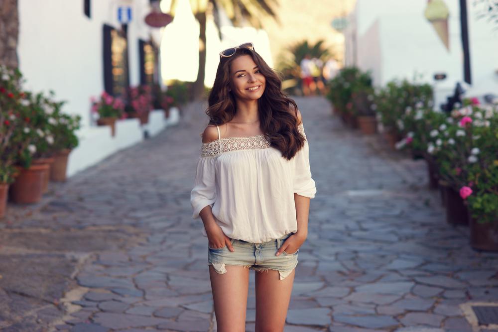 Ragazza in una via cittadina che indossa shorts in jeans sfrangiati in abbinamento ad una ampia blusa in cotone naturale con finiture in pizzo sulla parte alta e maniche a tre quarti.