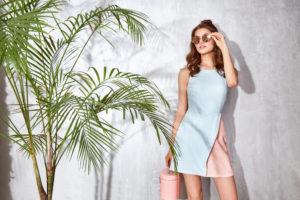 Ragazza che indossa un abito color block in cotone scivolato. Colori grigio e rosa. Borsa a secchiello in rosa