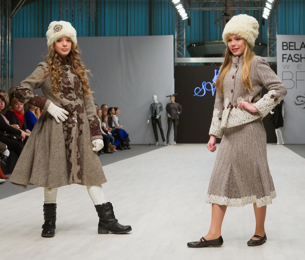 Due bambine ad una sfilata di moda che indossano abiti eleganti invernali con colbacchi di ecopelliccia