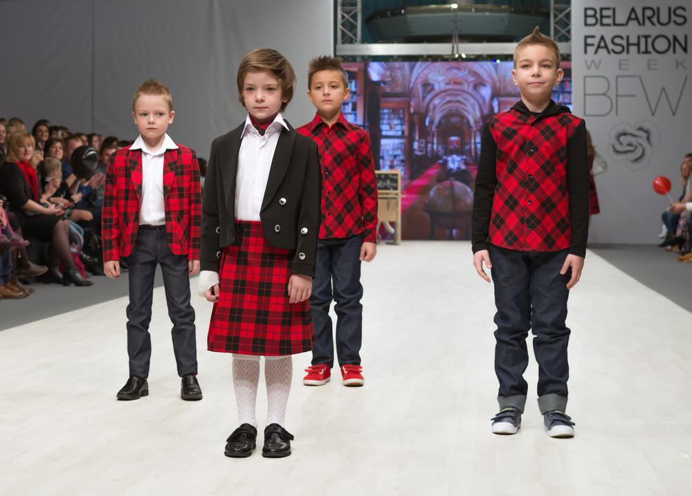 Gruppo di bimbi ad una sfilata che indossano abiti a scacchi stile scozzese