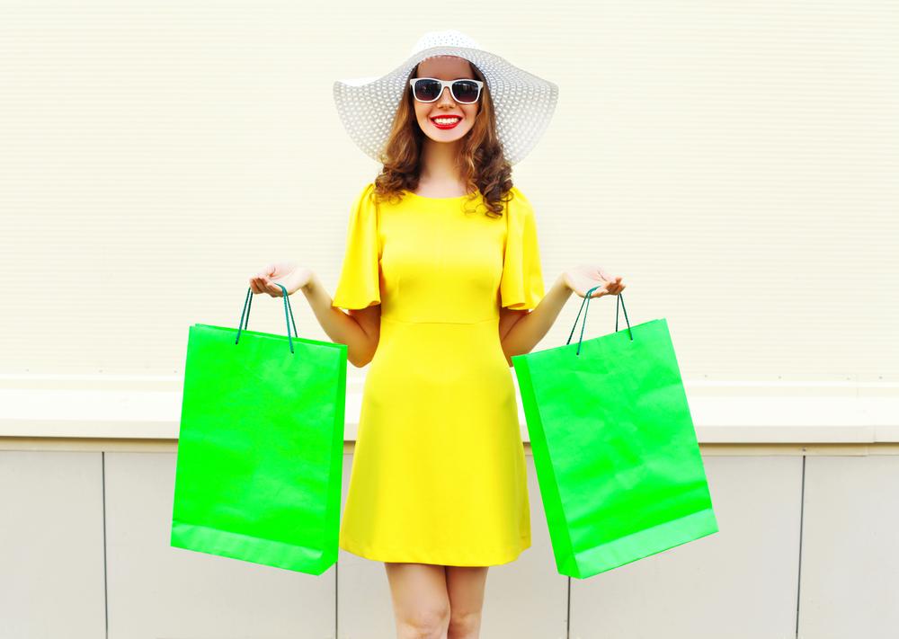 Ragazza che indossa un abito giallo limone con maniche a sbuffo e cappello bianco a tesa larga. porta nelle mani due grandi shopper verde acido