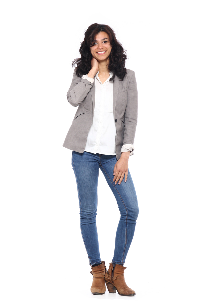 Ragazza che indossa Jeans a sigaretta azzurro chiaro, camicetta bianca e giacca grigio chiaro aperta. Completano l'outfit tronchetti color cuoio