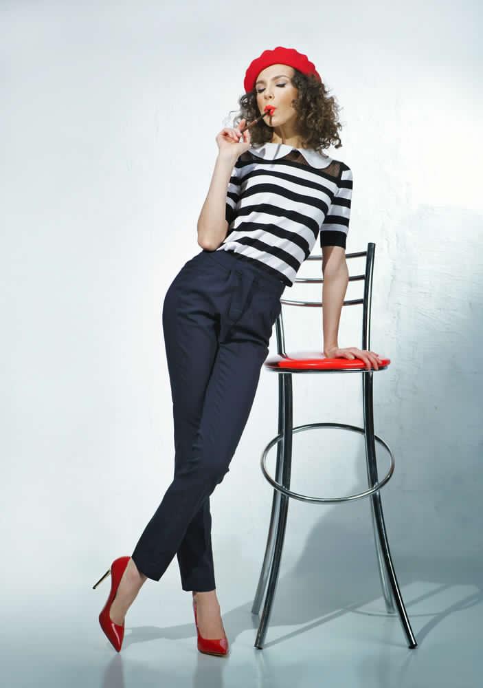 Ragazza appoggiata ad uno sgabello alto che indossa pantaloni a sigaretta neri abbinati ad una t shirt modello marina a grosse righe orizzontali. Completano l'outfit scarpe décolleté rosse e cappello modello coppola rosso in lana