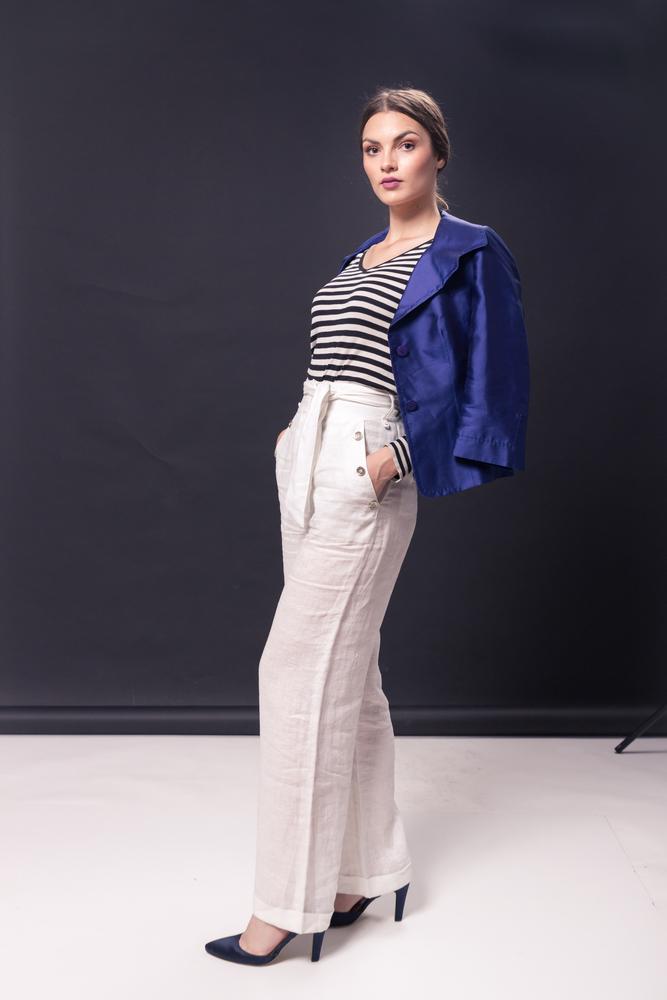 Ragazza a figura intera che indossa una T shirt modello marina a righe bianche e blu con scollo a V in abbinamento ad ampi pantaloni bianchi in lino, giacca in raso viola e décolleté nere