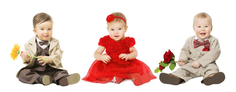 3 bimbi al di sotto dei 2 anni in abiti elegantissimi: i maschietti con giacca, gilet e papillon, la bimba con abito rosso in tulle e pizzo