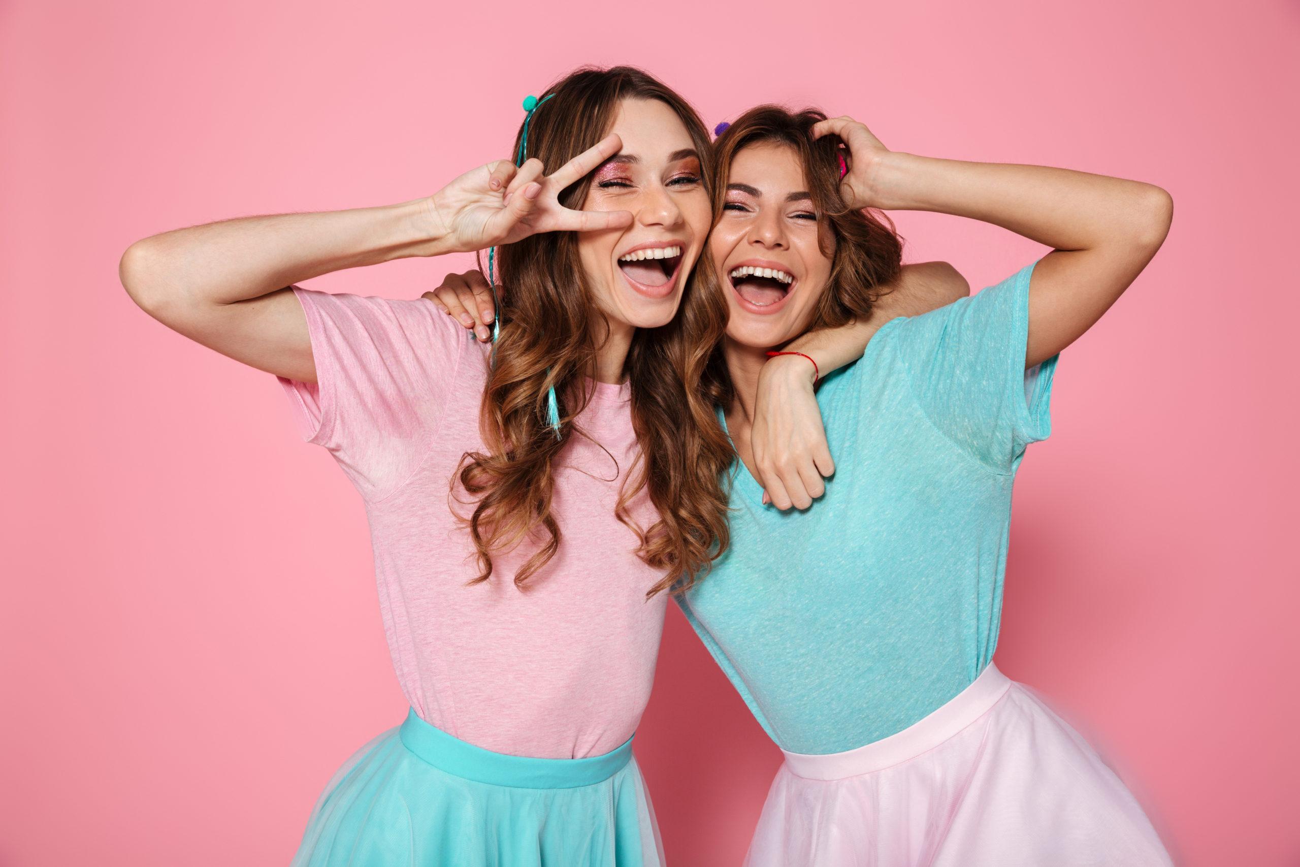 Due ragazze che indossano abbinamento di due colori. Uno con gonna turchese e t shirt rosa e l'altro con gonna rosa e t shirt turchese