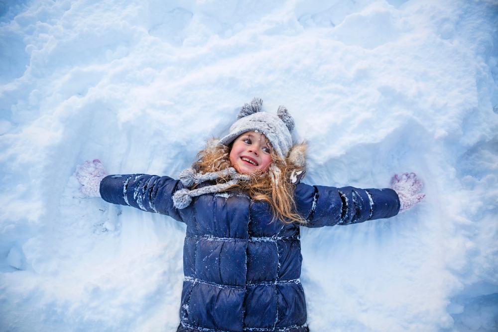 Bimba distesa nella neve. Indossa un piumino di colore blu e grande cappello con pon pon grigio